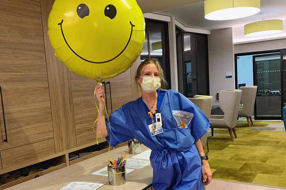 UVA Nursing grad Cate Rhangos (BSN `19) with giant happpy face balloon at Memorial Sloan Kettering Cancer Center in New York